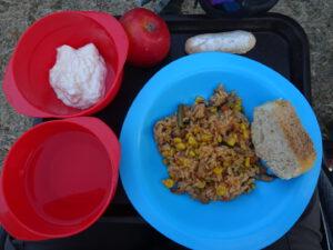maaltijd taize, prutje eten met stukje stokbrood op blauw bord, yoghurt in rood schaaltje en drinken in rood schaaltje